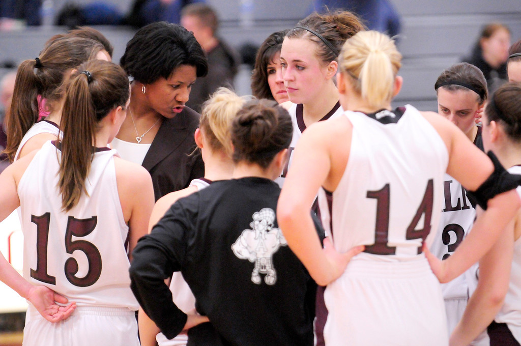 Description of . Alma women's basketball head coach Keisha Brown talks to her team at center court after their victory over Albion College on Saturday.