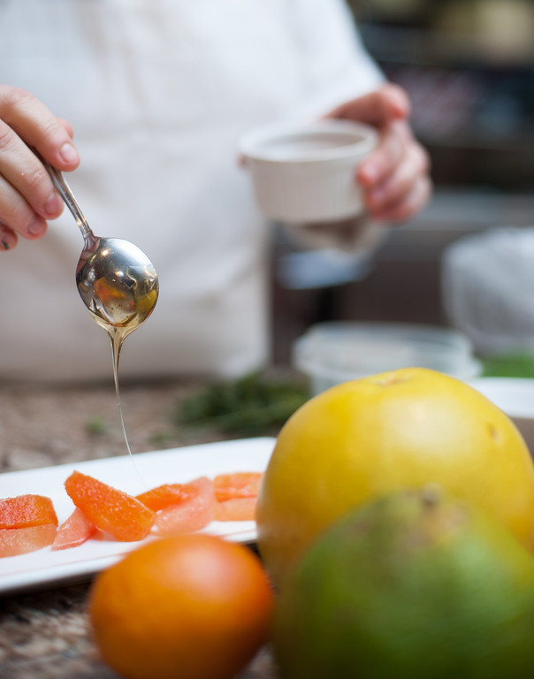 Description of . Emma Currie drizzles honey on her citrus salad with tarragon and honey at the Market on Main in downtown Mt. Pleasant, MI. (Sun photo by Holly Mahaffey/@hollymahaffey)