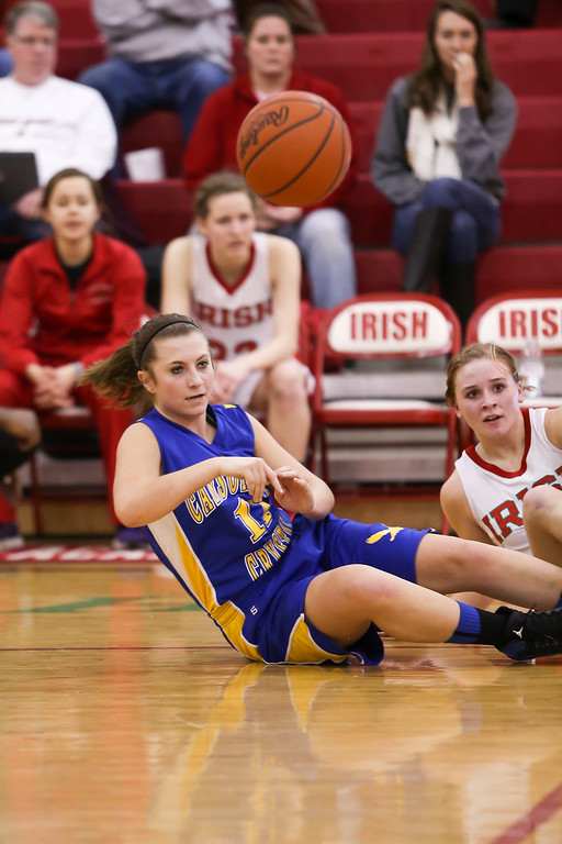 . Carson City-Crystal junior Mikayla Dufle, (11) throws a pass after tumbling over with Sacred Heart\'s Sara Hansen, (2) at Sacred Heart Thursday, Jan. 23, 2014. Carson City-Crystal won 50-23.  (Sun photo by KEN KADWELL/@KenKadwell).