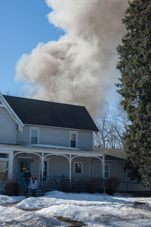 . Neighboring houses evacuate while firefighters battle a blaze in a garage on University in downtown Mount Pleasant. (Sun photo Holly Mahaffey/@hollymahaffey)